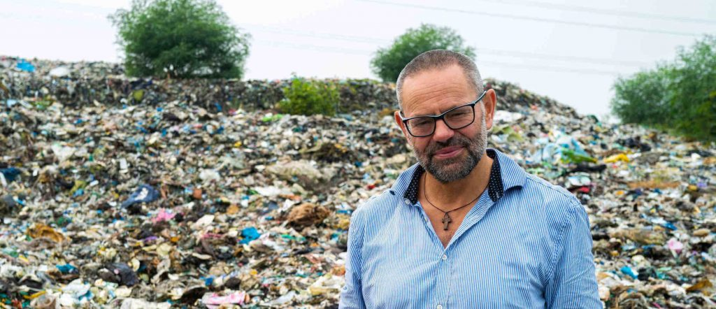 Martin Alvsvåg foran ramfor ein enorm avfallshaug i Vietnam i 2019. Foto: Edmond Yp Yang
